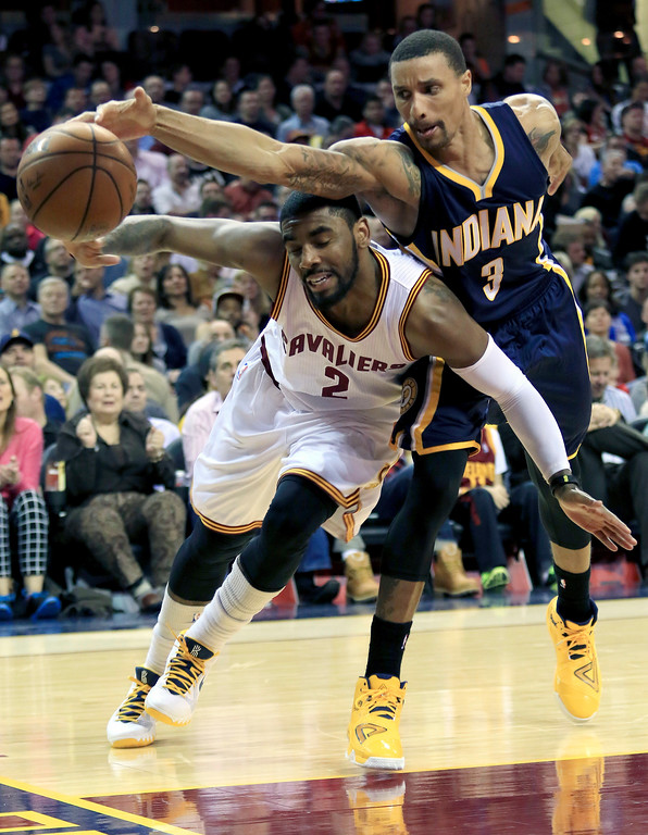 . Indiana Pacers George Hill (3) reaches over Cleveland Cavaliers Kyrie Irving for a loose ball in the second quarter during a NBA basketball game Friday March 20, 2015 in Cleveland. (AP Photo/Aaron Josefczyk)