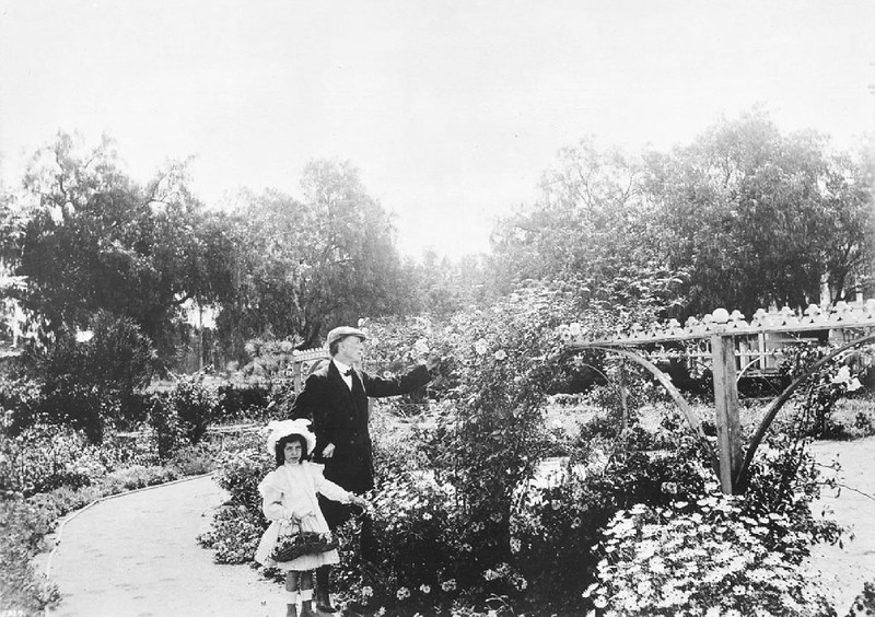 Paul deLongpre and his daughter in the garden of their residential house in Hollywood, ca.1910