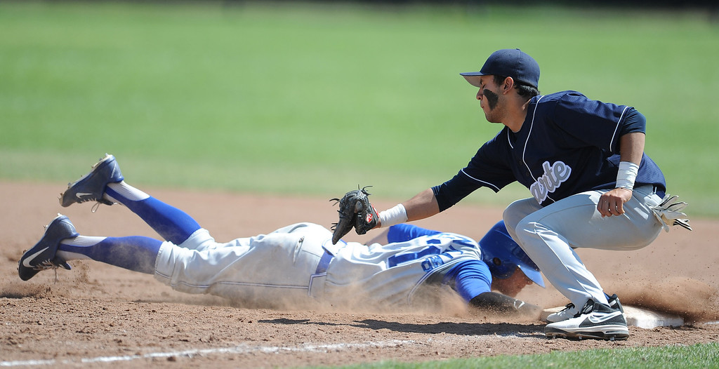 . Charter Oak\'s Kevin Ecternkamp (31) dives back safe at first ahead of the tag by Duarte first baseman Jonathon Sandoval in the third inning of the Championship game of the Gladstone Baseball Tournament at Gladstone High School on Wednesday, April 3, 2013 in Covina, Calif. Charter Oak won 5-3. (Keith Birmingham Pasadena Star-News)