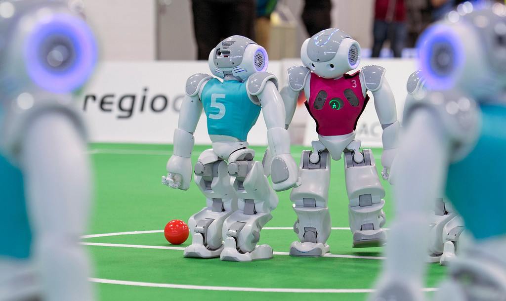 . Roboters play the ball during a soccer match at the RoboCup German Open 2014 in Magdeburg, Germany, Thursday, April 3, 2014. 44 international RoboCup Major League teams from 12 countries demonstrate the state-of-the-art competitions in soccer, rescue and service robots. The RoboCup German Open takes place from April 3 to April 5, 2014. (AP Photo/Jens Meyer)