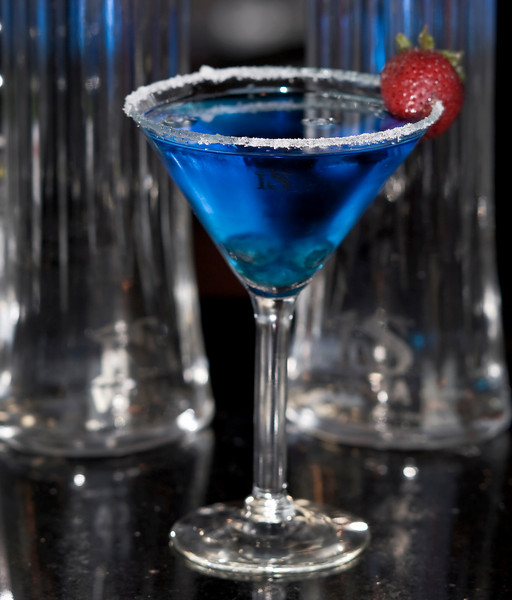 Download high quality free photograph of IS Blue Lagoon the new vodka martini from ISVodka made with 1.5 oz of ISVodka, 1 oz Blueberry Schnapps, .5 oz Blue Curacao and 3 blueberries and 1 strawberry for garnish. Add ISVodka, Blueberry Schnapps and Blue Curacao to ice-filled shaker... shake well. Rim a martini glass with sugar, then pour. Add blueberries and strawberry.