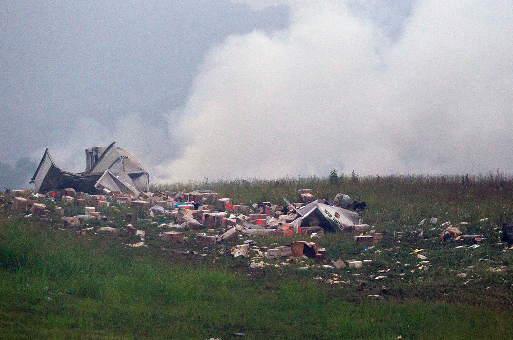 . Debris lies strewn as a UPS cargo plane rests on a hill at Birmingham-Shuttlesworth International Airport after crashing on approach, Wednesday, Aug. 14,  2013, in Birmingham, Ala.  (AP Photo/Butch Dill)