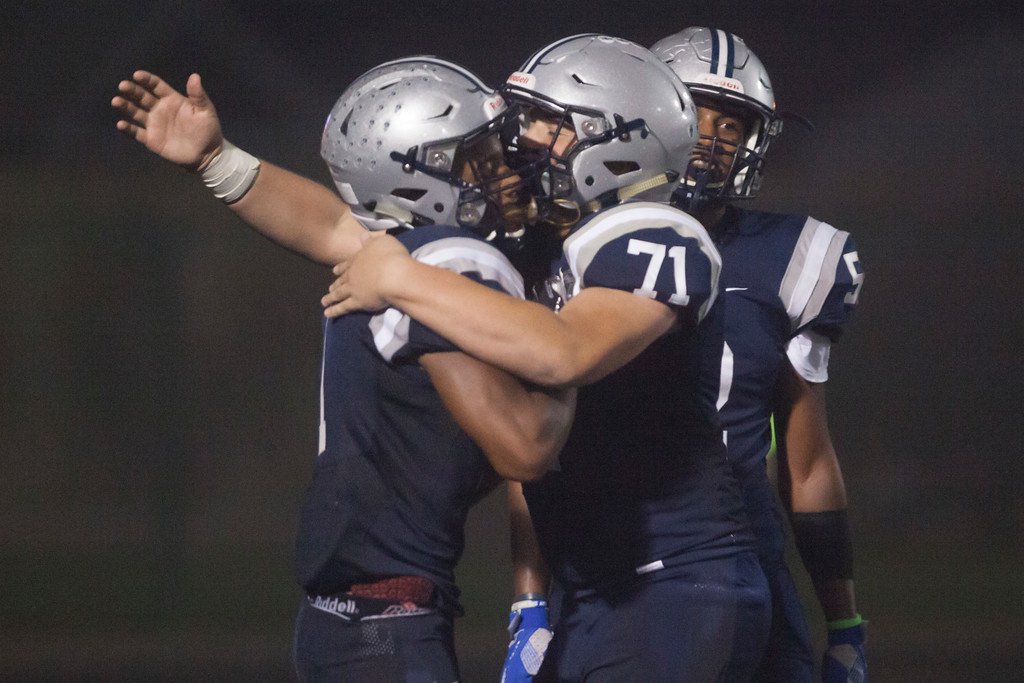 . Jen Forbus - The Morning Journal<br> Lorain\'s Tyshawn Lighty gets a celebratory hug from teammate Jacob Addis (71) after scoring a touchdown against St. Joseph on Sept. 14.