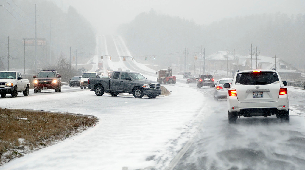 . Vehicles travel on US highway 280 as snow begins to make driving conditions difficult Tuesday January 28,  2014 in Chelsea,  Ala. A fast-moving, unexpectedly severe winter storm blanketed much of Alabama with a treacherous layer of frozen precipitation Tuesday.  (AP Photo/Hal Yeager)