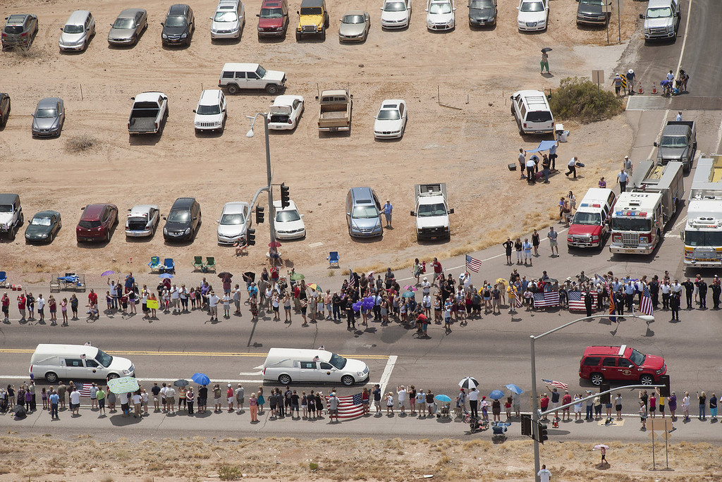 . People gather along the side of the highway as the procession for the 19 fallen firefighters of the Granite Mountain Hotshots crew makes its way to Prescott on July 7, 2013 in Phoenix, Arizona. The firefighters are transported by 19 hearses, each accompanied by motorcycle escorts from various agencies from Phoenix, Arizona to Prescott, Arizona. Nineteen of the twenty member crew died battling a fast-moving wildfire near Yarnell, Arizona on Sunday June 30th. (Photo by Laura Segall/Getty Images)