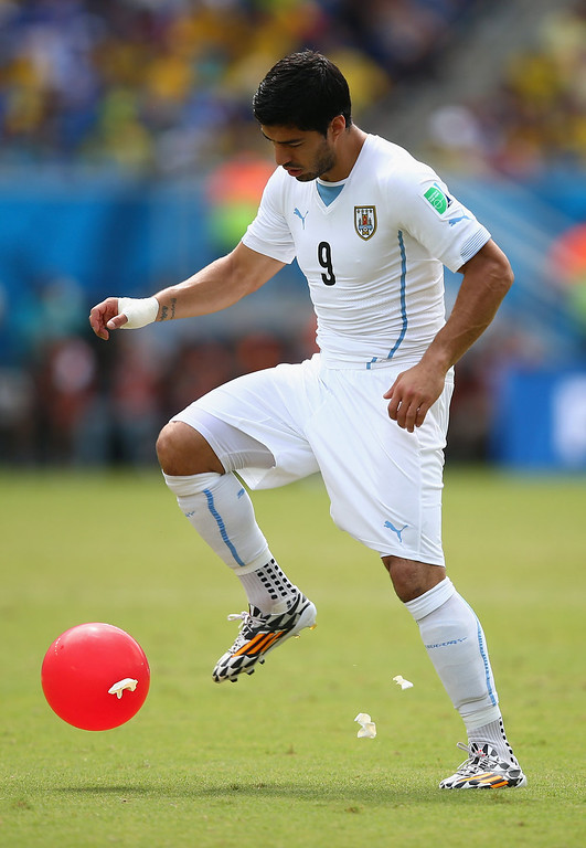 . Luis Suarez of Uruguay bursts balloons during the 2014 FIFA World Cup Brazil Group D match between Italy and Uruguay at Estadio das Dunas on June 24, 2014 in Natal, Brazil.  (Photo by Clive Rose/Getty Images)