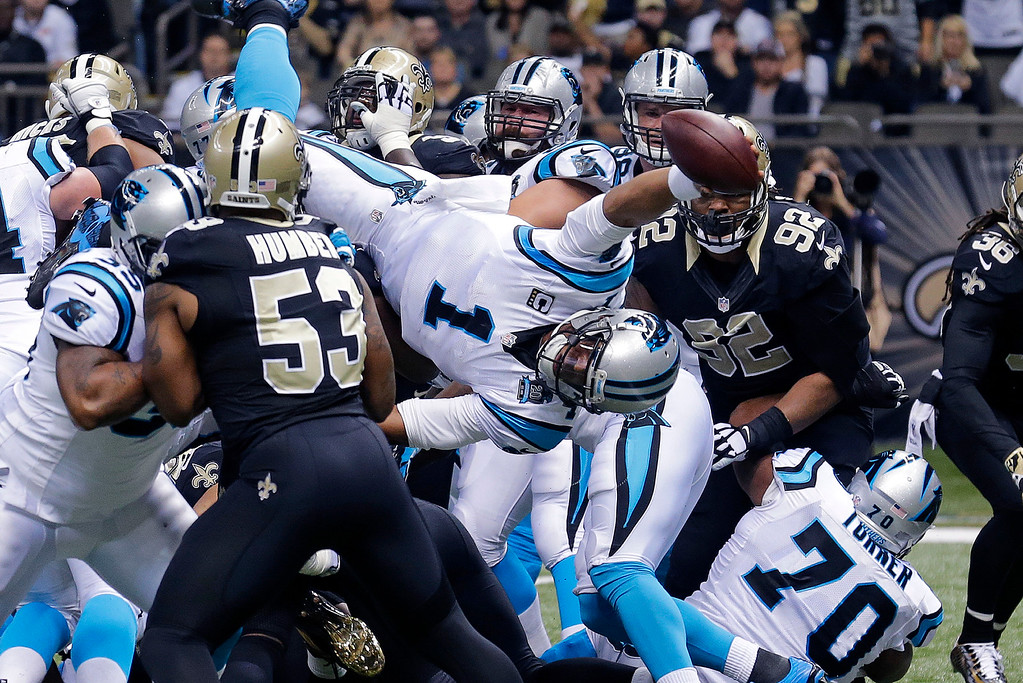 . Carolina Panthers quarterback Cam Newton (1) dives over the pile for a touchdown in the first half of an NFL football game against the New Orleans Saints in New Orleans, Sunday, Dec. 7, 2014. (AP Photo/Bill Haber)