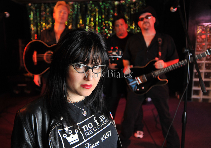"""Claudia Leo of """"No Fun Records"""" poses in front of  the band """"Horse Cave Trio"""" at The Club Above on Main St.  (Photo by Mark Bialek)"""