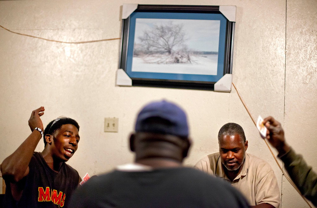 . Kyle Alexander, 20, left, plays cards with Kent Grovner, right, and fellow residents in The Trough, the only bar in the Hog Hammock community of Sapelo Island, Ga. on Thursday, May 16, 2013. (AP Photo/David Goldman)