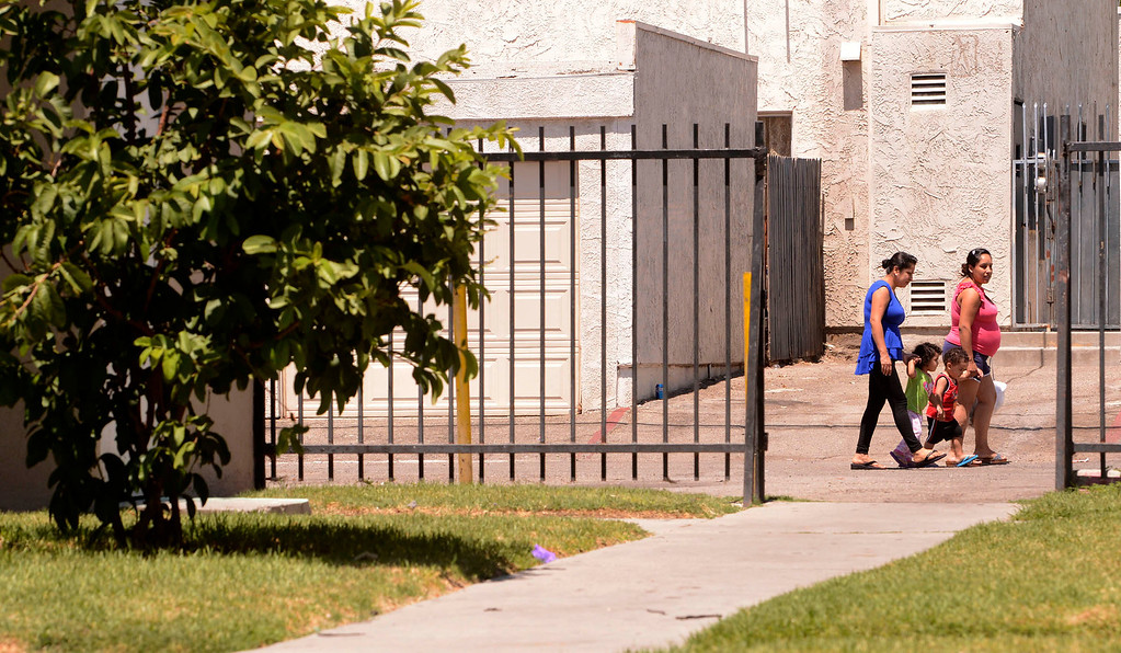 . Residents walk by the area where one victim ran to the sidewalk after being shot in a double-shooting at the Orchid Lane Apartments along the 300 block of Orchid Lane in Pomona August 11, 2013.   GABRIEL LUIS ACOSTA/STAFF PHOTOGRAPHER.
