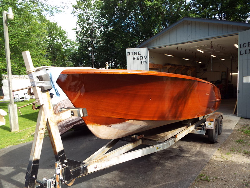Moving the hull out of the shop so we can get the fiberglass parts in the finish room. Front port view with all the varnish applied.