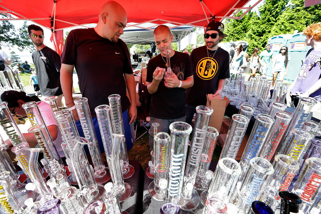 . Vendors look over their display of glass bongs at the first day of Hempfest, Friday, Aug. 16, 2013, in Seattle. Thousands packed the Seattle waterfront park for the opening of a three-day marijuana festival � an event that is part party, part protest and part victory celebration after the legalization of pot in Washington and Colorado last fall. Hempfest was expected to draw as many as 85,000 people per day. (AP Photo/Elaine Thompson)