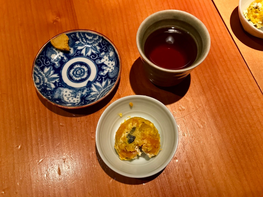 Tea, appetizer, and a small dish for tonkatsu sauce.