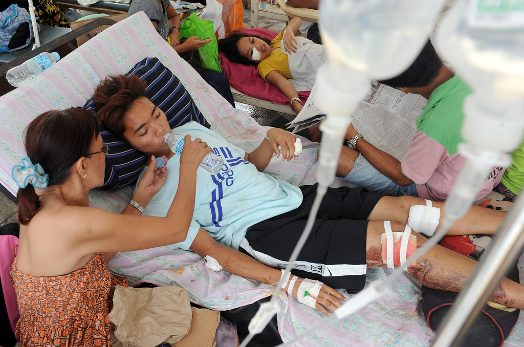 . University student John David Espanola, 19, one of more than 200 people injured during a 7.1-magnitude earthquake that hit the central Philippine island of Bohol on October 15, 2013, is comforted by his mother as he lays in a hospital bed in the parking lot of a government hospital in Tagbilaran city, the capital of Bohol island, on October 17, 2013. The quake struck the central Philippines on October 15, 2013, killing 161 people.   AFP PHOTO / Jay  DIRECTO/AFP/Getty Images