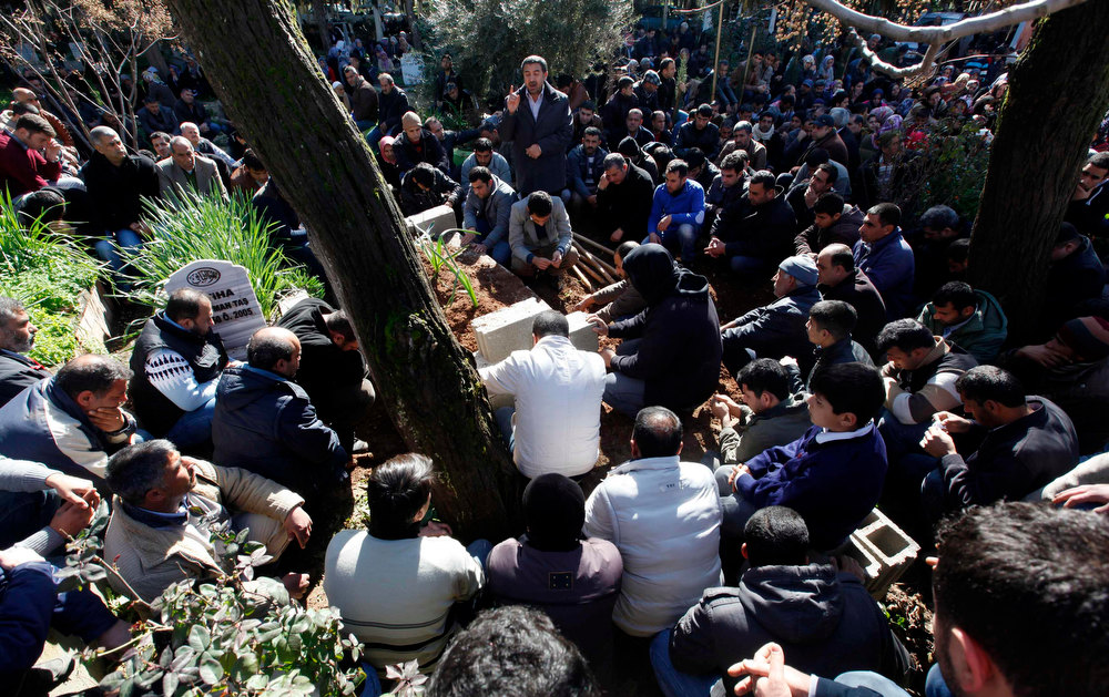 Description of . People attend the funeral of Ahmet Tas, 35, one of the 13 victims who died during an explosion at a crossing on Turkey's border with Syria, in the town of Reyhanli on the Turkish-Syrian border in Hatay province February 12, 2013. A Syrian minibus exploded at a crossing on Turkey's border with Syria near the Turkish town of Reyhanli on Monday, killing at least 13 people including Turkish citizens and wounding dozens more, Turkish officials said. REUTERS/Umit Bektas