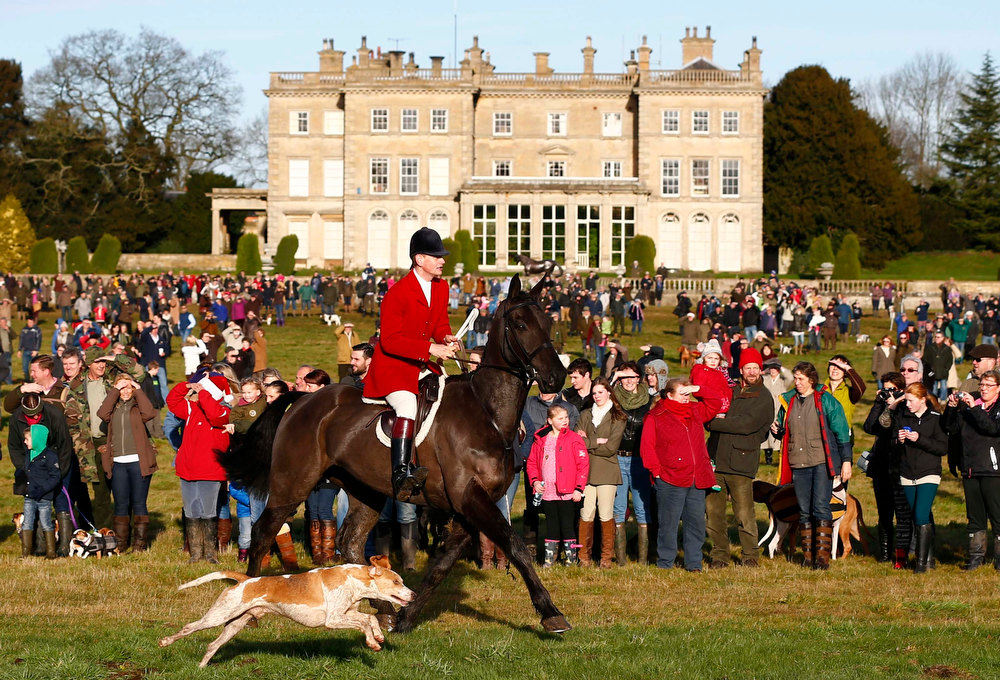. Spectators watch members of the Quorn hunt  during the traditional Boxing Day meet at Prestwold Hall near Loughborough, central England, December 26, 2012. A ban imposed seven years ago states that foxes can be killed by a bird of prey or shot but not hunted by dogs. Hunts continue nowadays with pursuers accompanying dogs in chasing down a pre-laid scented trail.  REUTERS/Darren Staples