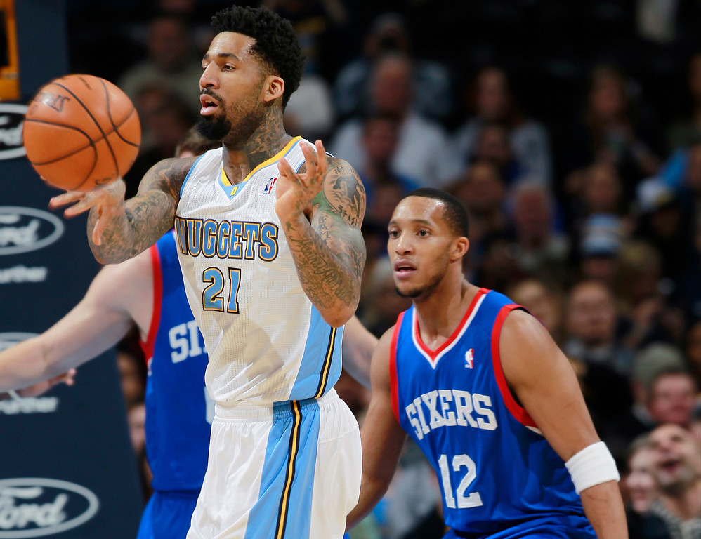 . Denver Nuggets forward Wilson Chandler, front, passes the ball away from Philadelphia 76ers center Spencer Hawes, back left, and guard Evan Turner during the first quarter of an NBA basketball game in Denver on Wednesday, Jan. 1, 2014. (AP Photo/David Zalubowski)
