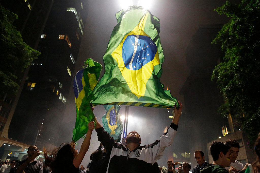 . Demonstrators wave their country\'s national flag on Paulista Avenue where crowds gathered to celebrate the reversal of a fare hike on public transportation, in Sao Paulo, Brazil, Thursday, June 20, 2013. (AP Photo/Nelson Antoine)