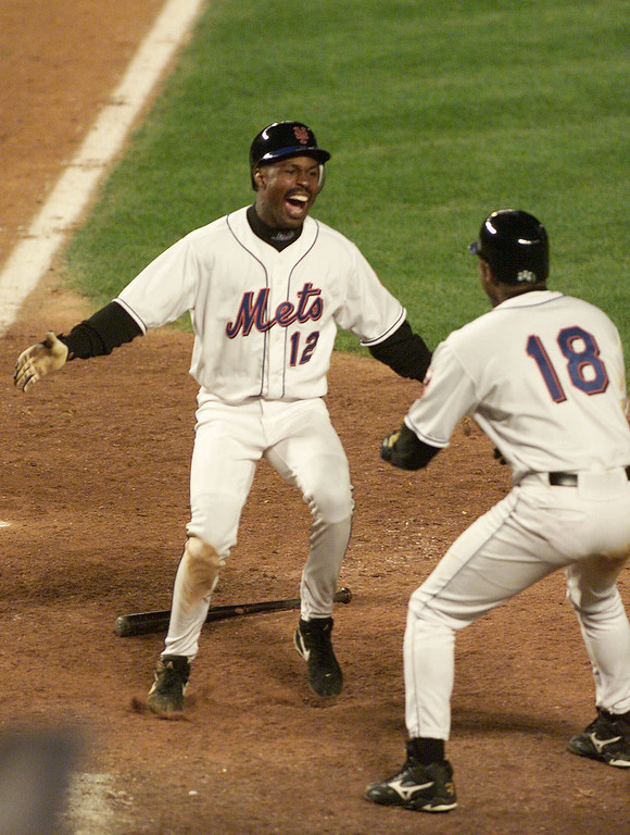 . New York Mets Shawon Dunston, left, and Darryl Hamilton celebrate after Dunston scored the winning run in the 11th inning against the Pittsburgh Pirates, Friday, Oct. 1, 1999, in New York. The Mets won 3-2 and kept their playoff hopes alive. Dunston scored on teammate Robin Ventura\'s single. (AP Photo/Jeff Zelevansky)