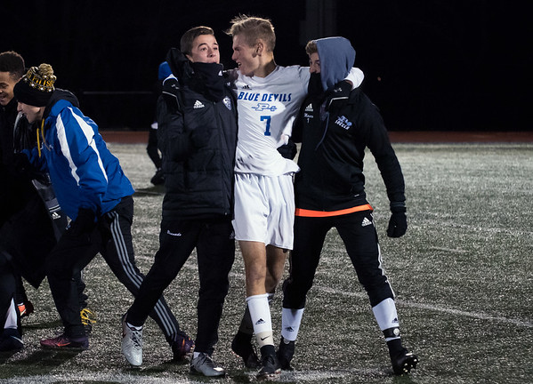11/14/18 Wesley Bunnell | Staff Plainville #23 vs Stonington #3 soccer in the Class M Semifinal at Xavier High School on Wednesday night. Tyler Miller (7) celebrates with teammates.