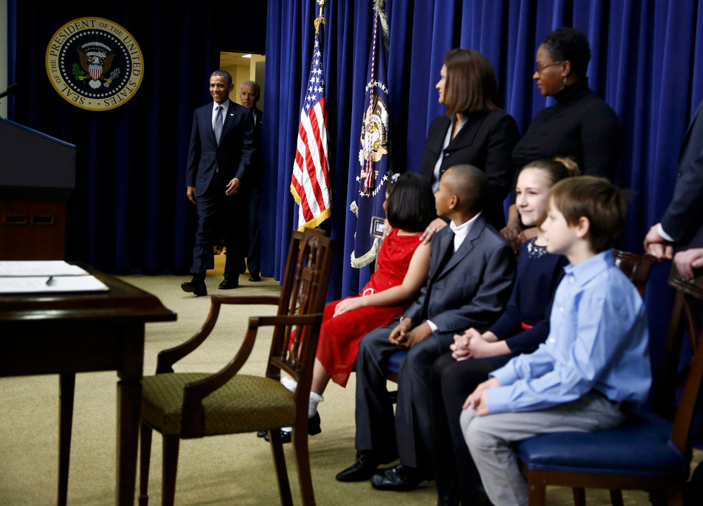 Description of . U.S. President Barack Obama (L) and Vice President Joe Biden arrive to unveil a series of proposals to counter gun violence during an event at the White House in Washington January 16, 2013. Seated at right, are children and the families of children who wrote to the president following  the December 14, 2012 school shooting in Newtown, Connecticut, in which 20 children and six adults were killed.  REUTERS/Jason Reed