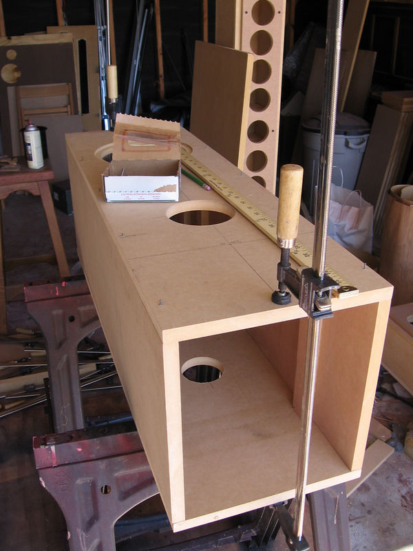 """Align the side panels with the edges of the front panel, clamp, and drill nail holes about 1"""" deep at the pencil marks using a 5/64 drill bit. (You must use this exact size drill bit so the nails will fit perfectly in the holes yet can be pulled out by hand). The nails will slip easily into their pilot holes and stand about 1/4"""" to 1/2"""" proud. Notice now nicely the front and side panels are aligned at the seam, but not the bottom panel which I will do later. Click on the picture to enlarge it to better see the nails in place."""