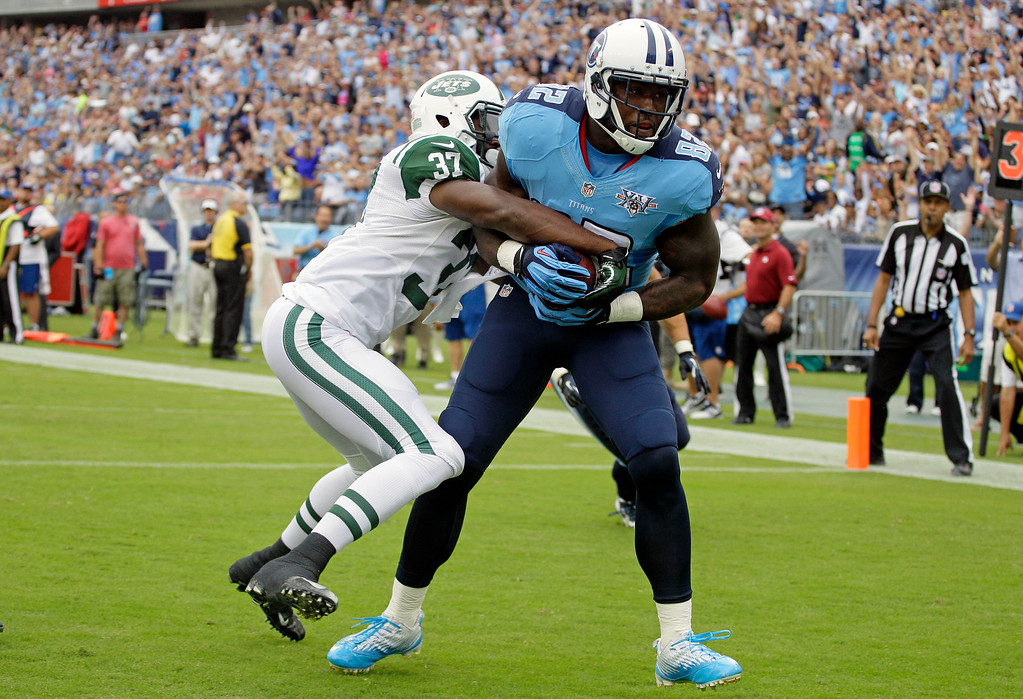 . Tennessee Titans tight end Delanie Walker (82) hangs onto the ball as New York Jets free safety Jaiquawn Jarrett (37) tries to knock it loose as Walkers scores a touchdown on a 1-yard pass in the first quarter of an NFL football game on Sunday, Sept. 29, 2013, in Nashville, Tenn. (AP Photo/Wade Payne)