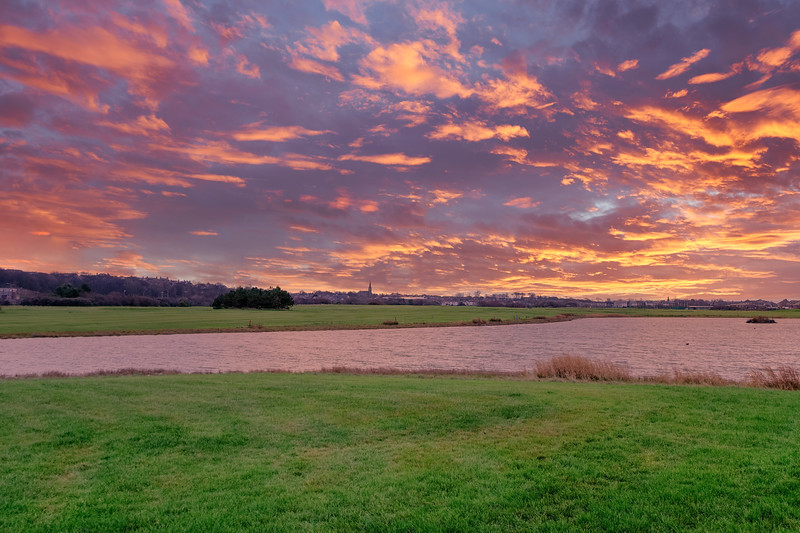 Looking Over the Auchenharvie  lake and Driving Range to the Town of Stevenston in the Far Distance at Sunset with a Blazing Red sky..