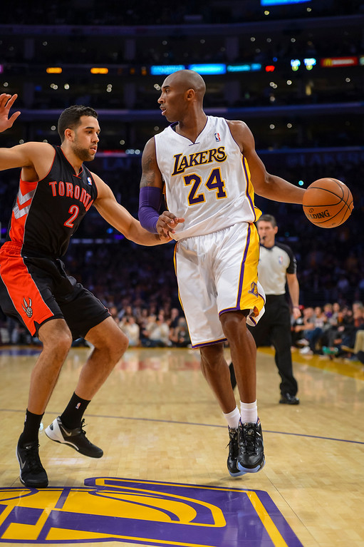 . Lakers� Kobe Bryant looks for a pass around Raptors� Landry Fields during first half action at Staples Center Sunday, December 8, 2013.   ( Photo by David Crane/Los Angeles Daily News )