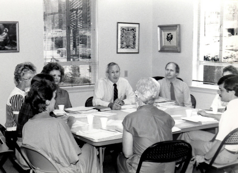 Rev. Dr. Henry Roberts (dark tie) meets with staff members.