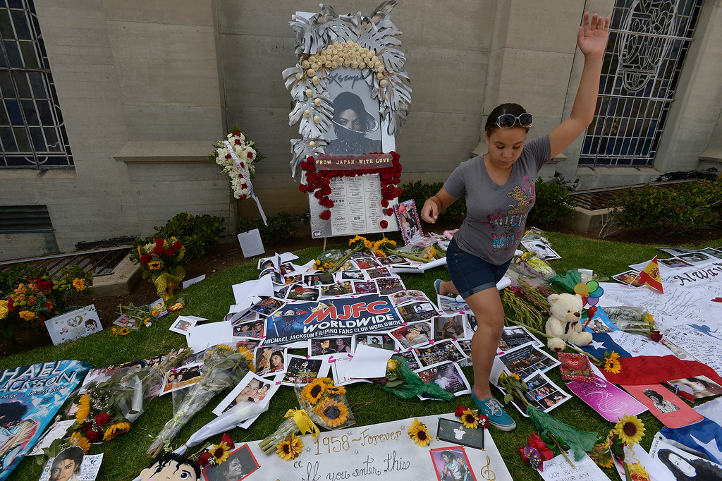 . A young fan jumps her way over remembrances. Michael Jackson impersonators, and fans gathered at the Great Mausoleum at Forest Lawn Memorial Park in Glendale to honor Jackson on the 5th anniversary of his death.  Glendale, CA. 6/25/2014 (Photo by John McCoy Daily News)