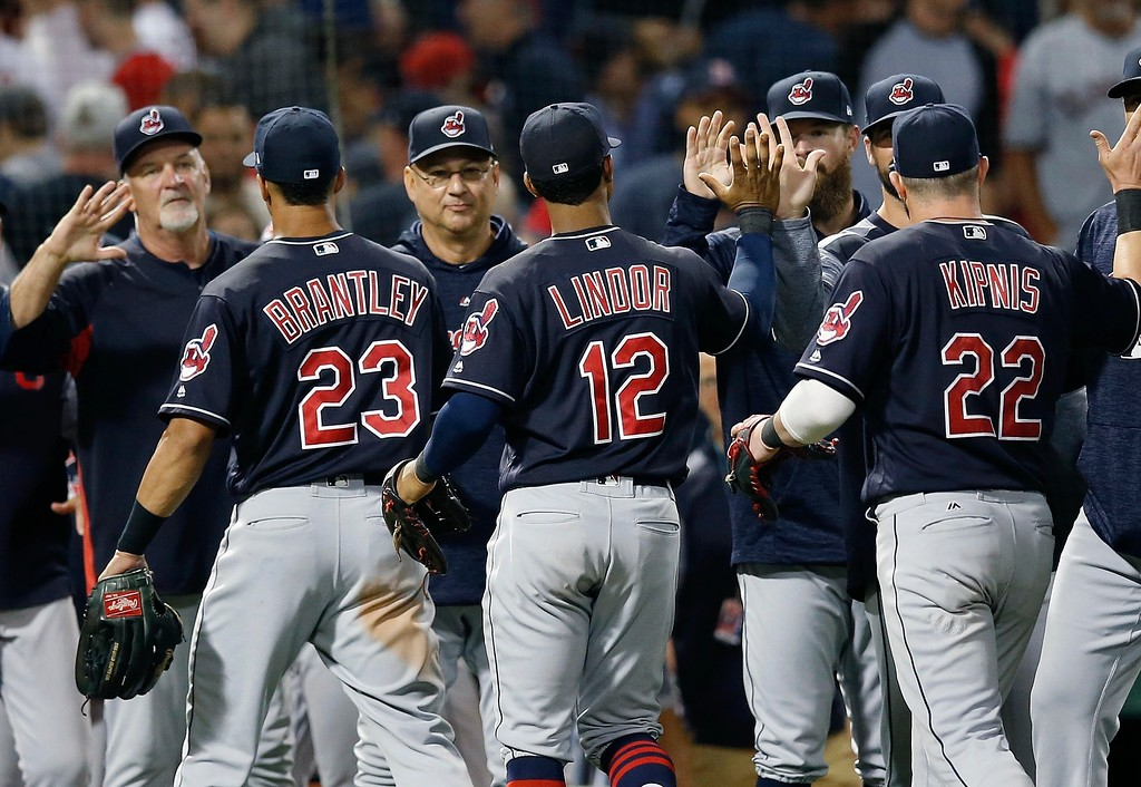 . Cleveland Indians\' Michael Brantley (23), Terry Francona center left, Francisco Lindor (12) and Jason Kipnis (22) celebrate after defeating the Boston Red Sox during a baseball game in Boston, Tuesday, Aug. 21, 2018. (AP Photo/Michael Dwyer)
