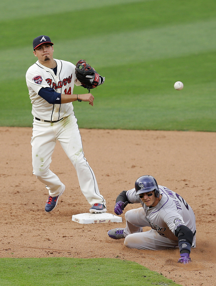 . Second baseman Ramiro Pena #14 of the Atlanta Braves turns a double play while shortstop Troy Tulowitzki #2 of the Colorado Rockies slides in the seventh inning of the game at Turner Field on May 24, 2014 in Atlanta, Georgia.  (Photo by Mike Zarrilli/Getty Images)