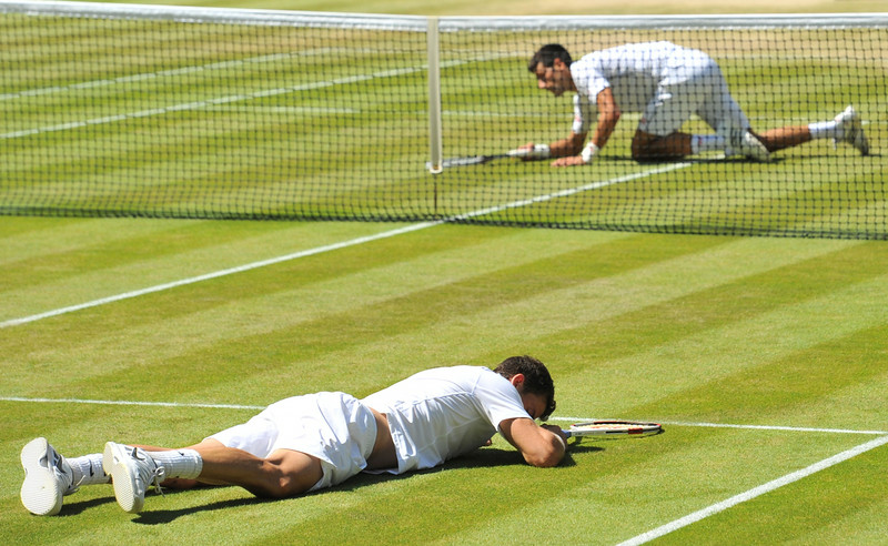 . Bulgaria\'s Grigor Dimitrov (front) and Serbia\'s Novak Djokovic (back) slip and fall down during their men\'s singles semi-final match on day 11 of  the 2014 Wimbledon Championships at The All England Tennis Club in Wimbledon, southwest London, on July 4, 2014. (GLYN KIRK/AFP/Getty Images)