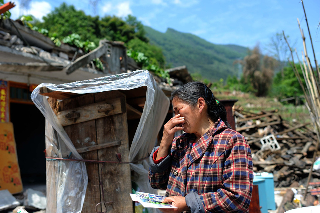. This photo taken on April 24, 2013 shows an elderly woman crying on seeing the photos of her grandson Zichen, who died during the earthquake in Ya\'an, in southwest China\'s Sichuan province. The April 20 earthquake killed at least 193 people and injured more than 12,000, and left tens of thousands of homeless survivors living in makeshift tents or on the streets, facing shortages of food and supplies.  AFP/Getty Images