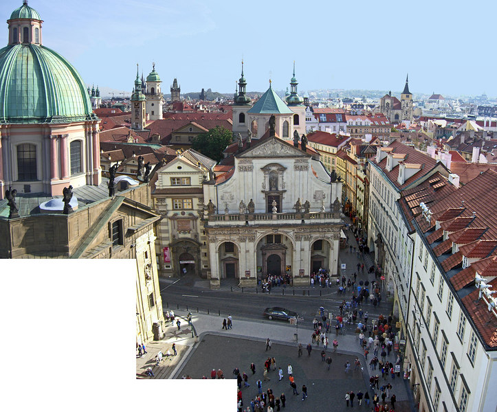 This is a montage of 3 photos taken from the East Tower. It looks east at the Church of the Holy Saviour. In the foreground is the paved court between the church and the bridge (which is behind us). The clock tower at the Old Town Square can be seen on the horizon about a third of the way from the left edge of the montage.