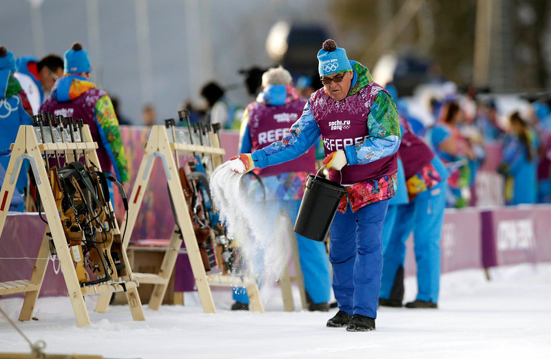 . A referee throws salt on the track prior to  the men\'s biathlon 20k individual race, at the 2014 Winter Olympics, Thursday, Feb. 13, 2014, in Krasnaya Polyana, Russia. (AP Photo/Lee Jin-man)