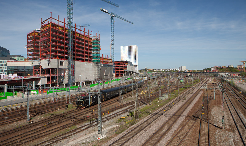 Rc6 pulls a passenger train out of Hagalund coach yard through Solna past the construction site of the Mall of Scandinavia.