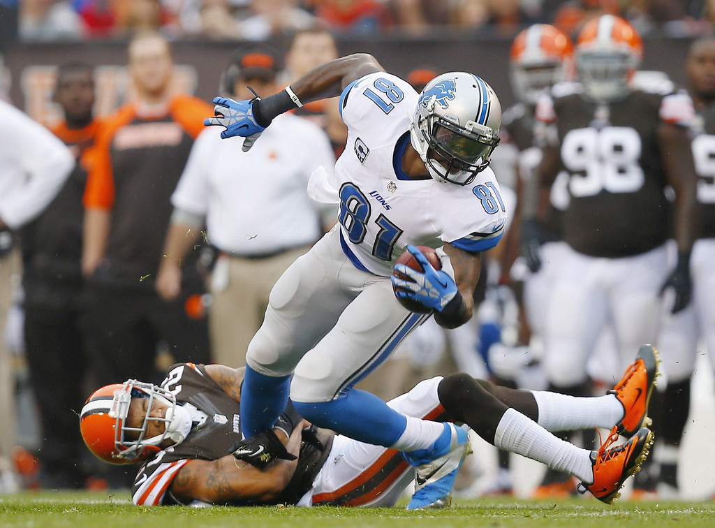. Wide receiver Calvin Johnson #81 of the Detroit Lions is hit by defensive back Joe Haden #23 of the Cleveland Browns at FirstEnergy Stadium on October 13, 2013 in Cleveland, Ohio.  (Photo by Matt Sullivan/Getty Images)