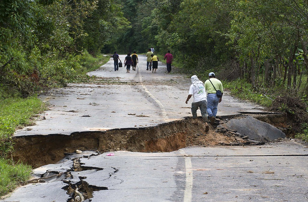 . Residents walk along a road leaving La Pintada, state of Guerrero, Mexico, on September 19, 2013 as heavy rains hit the country. AFP PHOTO/RONALDO  Schemidt/AFP/Getty Images