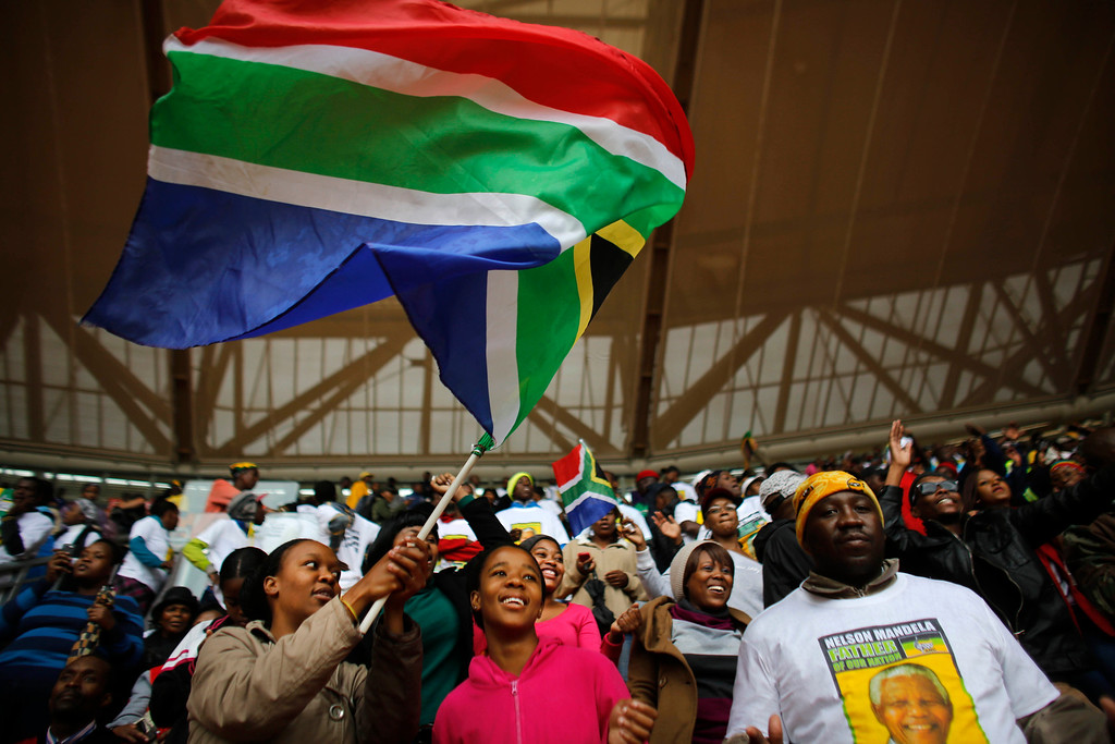 . A woman waves a South African national flag ahead of the memorial service for former South African president Nelson Mandela at the FNB Stadium in Soweto, near Johannesburg, South Africa, Tuesday Dec. 10, 2013. (AP Photo/Markus Schreiber)