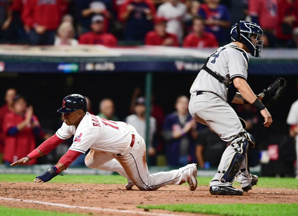 . Cleveland Indians\' Jose Ramirez, left, scores as New York Yankees catcher Gary Sanchez waits for the throw during the fifth inning of Game 1 of a baseball American League Division Series, Thursday, Oct. 5, 2017, in Cleveland. (AP Photo/David Dermer)