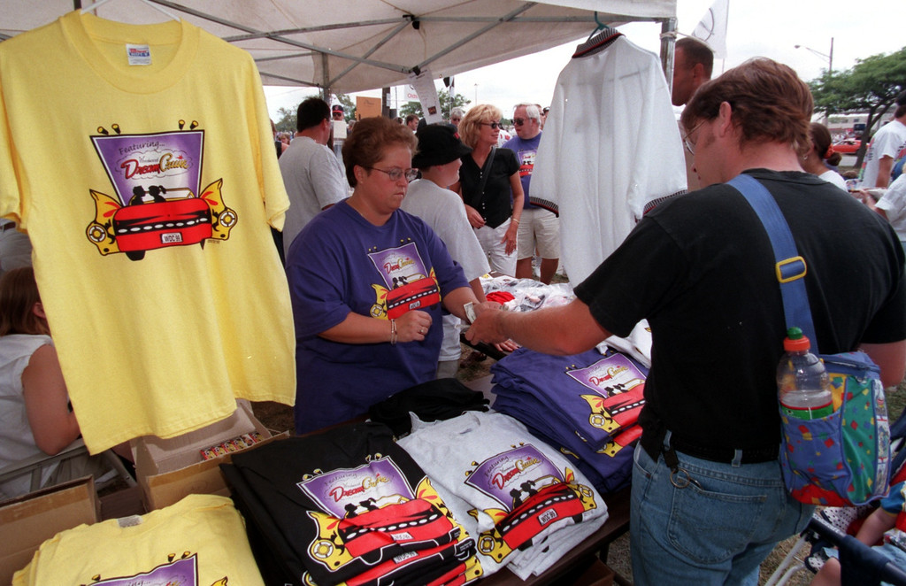 . Patti Moyer, left, sells Woodward Dream Cruise T-Shirts with the money going twords the Boy\'s & Girls Club during the Fifth Annual Woodward Dream Cruise.