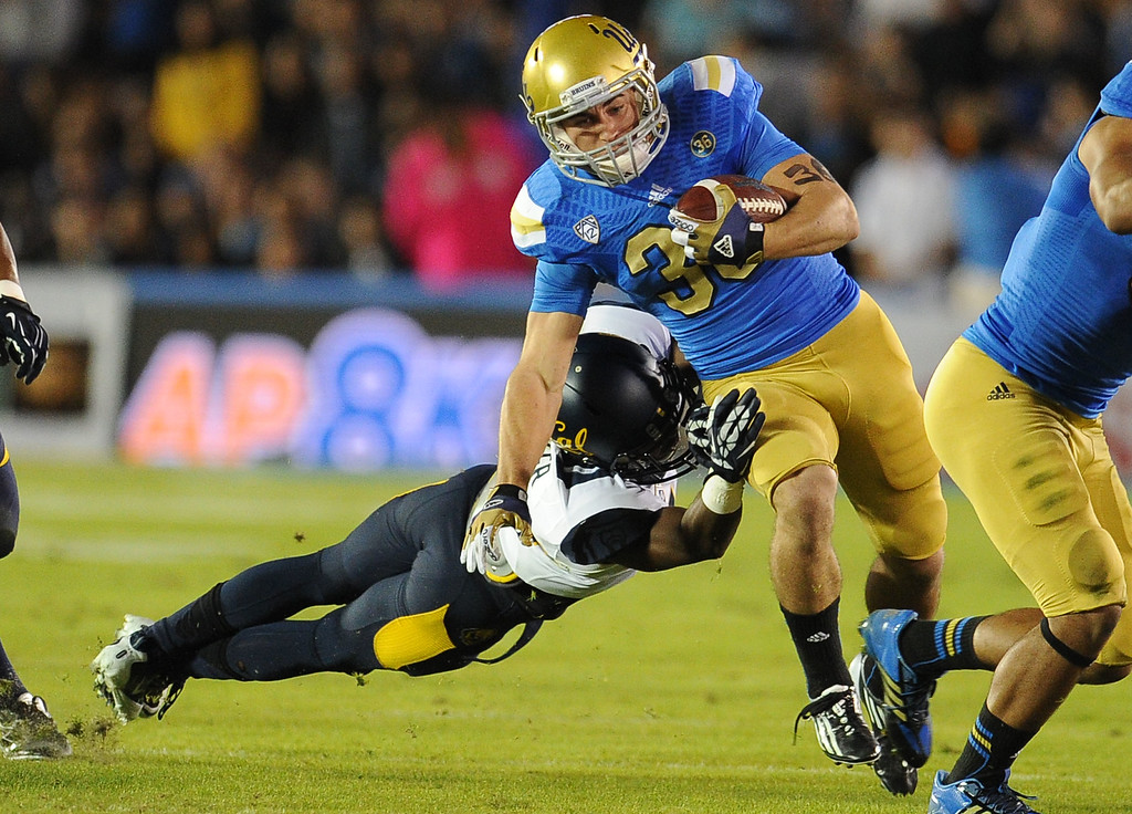 . UCLA running back Steven Manfro (33) runs away from California after catching a pass for a 14-yard first down against California during the first half of their college football game in the Rose Bowl in Pasadena, Calif., on Saturday, Oct. 12, 2013.   (Keith Birmingham Pasadena Star-News)