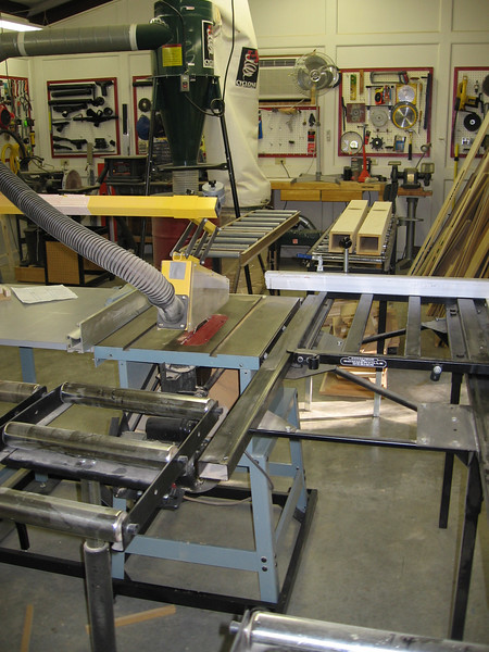 """Delta 12"""" commercial table saw with eight roller tables to handle a 4X8 sheet of mdf without assistance. Partially completed Zigmahornets in the background."""