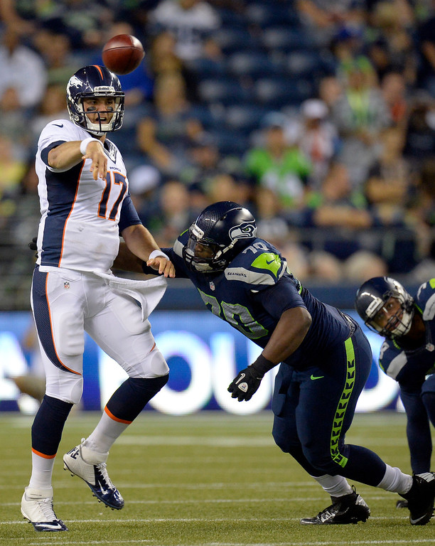 . SEATTLE, WA. - AUGUST 17: Denver Broncos quarterback Brock Osweiler (17) gets pressure from Seattle Seahawks defensive tackle Michael Brooks (70) during the fourth quarter August 17, 2013 at Century Link Field. (Photo By John Leyba/The Denver Post)