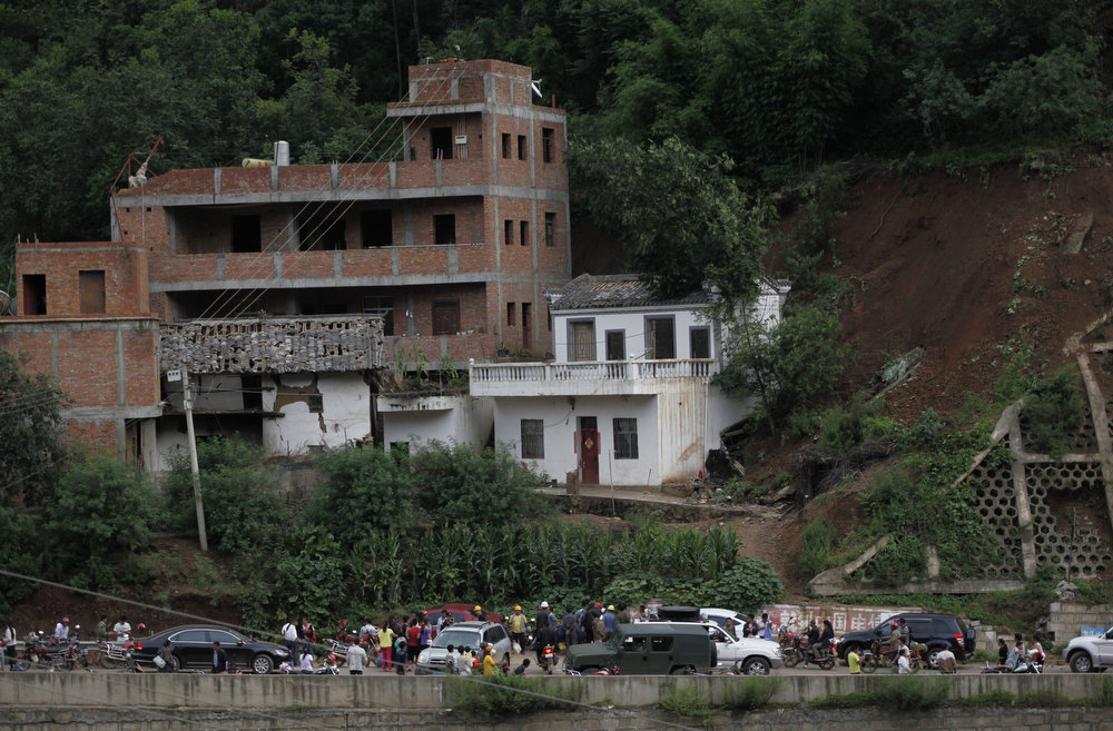 . Residents gather near damaged houses following an earthquake in an area of Ludian county in Zhaotong in southwest China\'s Yunnan province on August 3, 2014. At least 150 people were killed and 1,300 injured after a strong earthquake hit southwest China\'s mountainous Yunnan province, state media said. The quake in Zhaotong prefecture, in the province\'s northeast, toppled buildings and left residents frantically searching for survivors beneath the rubble, images on social media showed.  STR/AFP/Getty Images