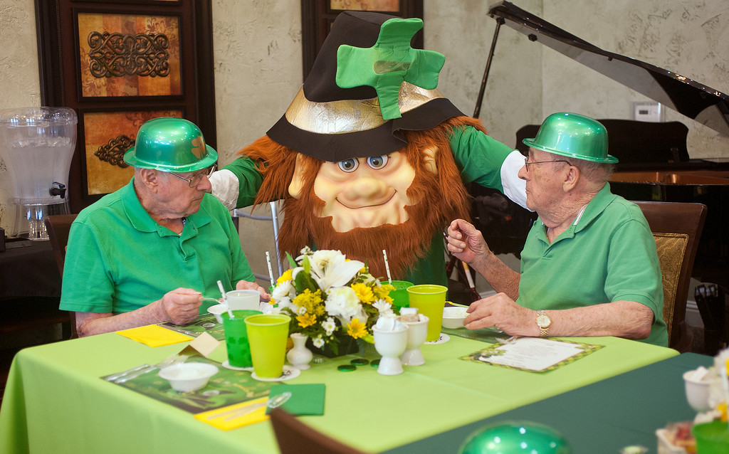 . A larger than life leprechaun played by activities director Susan Fry greets residents Paul Glass, 89, left, and Jack Moore, right, during the St. Patrick\'s Day party at Prestige Estates in Tyler, Texas, Tuesday, March 17, 2015. (AP Photo/The Tyler Morning Telegraph, Sarah A Miller)