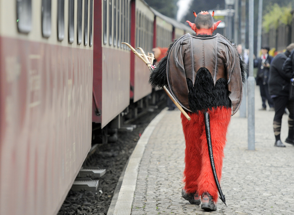 . A man costumed as a devil walks besides a small train in Schierke, central Germany, Tuesday, April 30, 2013. Hundreds of costumed devils and witches meet to celebrate Walpurgis Night, a traditional religious holiday of pre-Christian origins. The event is named after St. Walburga, an English nun who helped convert the Germans to Christianity in the 8th century. (AP Photo/Jens Meyer)