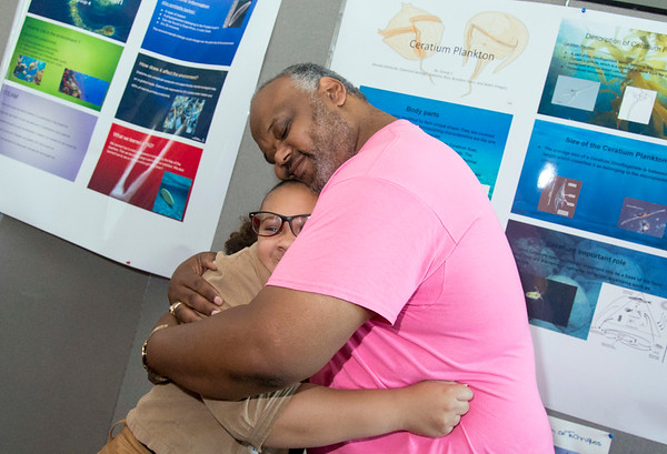 08/16/19 Wesley Bunnell | Staff TRIO, a two week long summer program run by CCSU in science and arts held their closing ceremony on Friday August 16, 2019 at Founders Hall at CCSU. Dalianiss Rios, a rising 8th grade at Betances STEM Magnet School, receives a hug from Berwyn Kelley after giving an overview of her science project hanging behind them. Kelley was invited by the family to the ceremony after working with Dalianiss previously at the New Britain Boys and Girls Club.